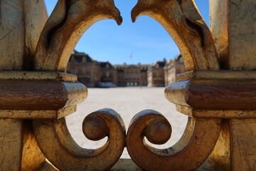 Château de Versailles, cour royale vue à travers une volute en fer forgé de la grille royale, portail d'entrée du palais (France)