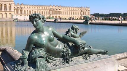 Statue de femme en bronze, allégorie de la Saône, au bord du parterre d'eau devant le château de Versailles (France)
