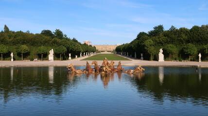 Jardins du château de Versailles en été, panorama depuis le bassin d'Apollon, avec la fontaine du char d'Apollon, des arbres et leur reflet dans l'eau (France)