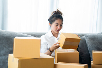 Woman packing and check address customers who order shopping online,work from home and delivery concept for COVID-19 new normal prevention