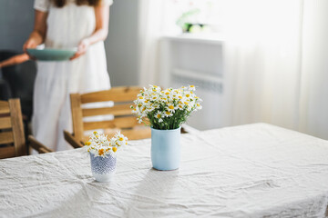 Table with flowers chamomile on linen tablecloth in the living room, bright interior, Cottagecore...