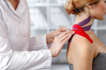Kinesiology taping. Physical therapist applying kinesiology tape to patient neck. Therapist treating injured trapezius muscles of young athlete. Post traumatic rehabilitation, sport physical therapy.