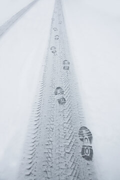 Shoeprints and tyre print in snow on rural winter road