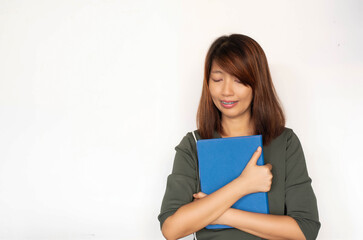 Lady hugging book in her arm,turn face down and smile,model posing