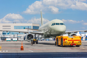 Towing a passenger plane using special equipment for aircraft maintenance. Departure flight in the background of the terminal building.