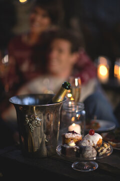 Close up of champagne bottle in metal wine cooler, glass cake stand with selection of cakes, person in the background.