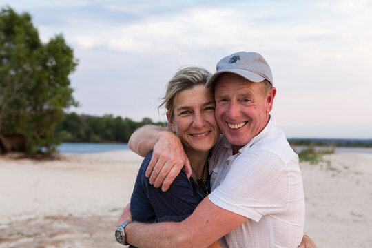 Mature couple embracing o the banks of the Zambezi River.