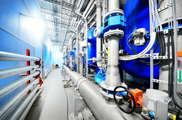 Large blue tanks in a industrial city water treatment boiler room. Wide angle perspective