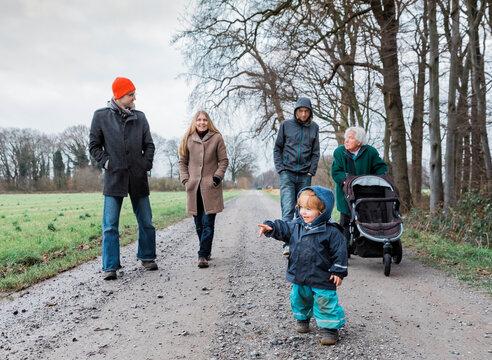 Multi-generational family walking on footpath
