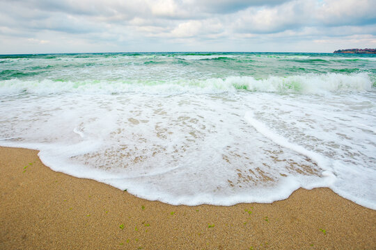 green sea waves beneath a grey sky. tide rolling on the beach. empty calm scenery. loneliness concept