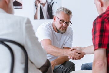 Men shaking hands during psychotherapy for people with addictions