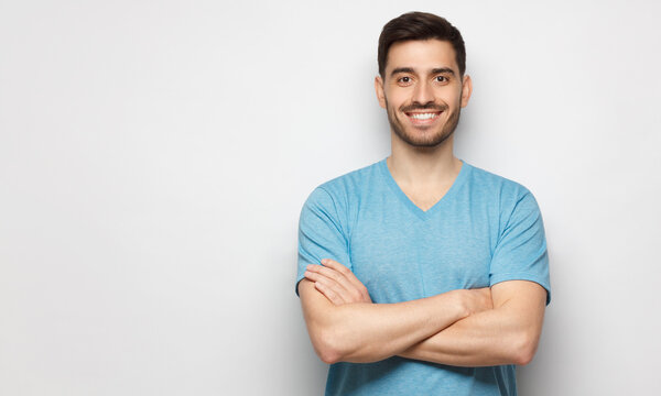 Banner of young handsome man wearing blue t-shirt, standing with crossed arms, isolated on studio gray background