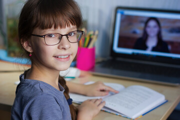 Distance learning online education. A happy girl studies at home and does school homework by internet