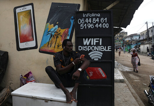 Lanssine Sylla checks his mobile as he sits next to a call center in a street of Adjame in Abidjan, Ivory Coast