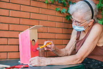 old woman with face mask painting a birdhouse