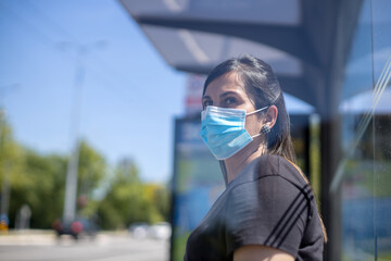 woman with face mask waiting for a bus