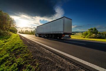 Fotobehang - White truck driving on the asphalt road in rural landscape at sunset with dark storm cloud