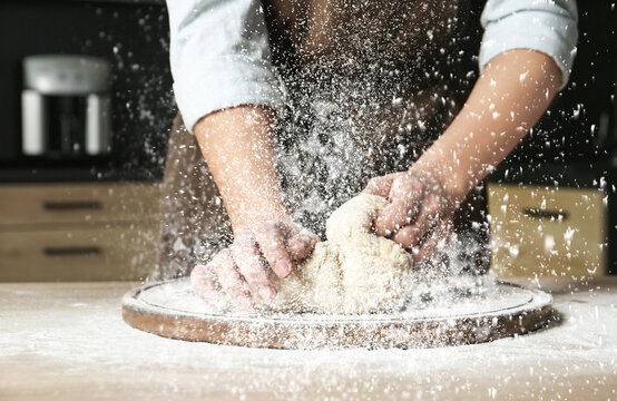 Young woman kneading dough at table in kitchen, closeup
