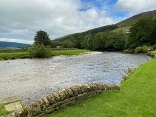 Fototapeta The river Wharfe, as it flows past the village of Burnsall, with trees and hills in the distance in, Burnsall, Skipton, UK