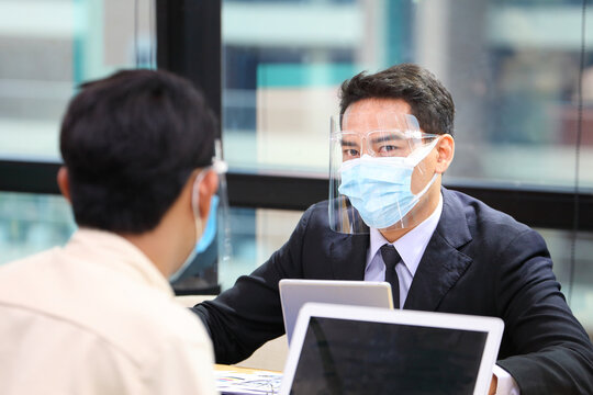 Businessman in formal wear with protective facial mask discussing with colleague in business office following new normal and social distancing policy during covid-19 or coranavirus pandemic outbreak