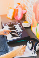 male amateur songwriter playing keyboard and writing a song on white music sheet in modern loft living room