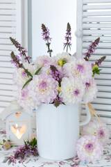 romantische Dekoration mit Dahlienstrauß in Weiß und Lila und Laterne mit Herzmotiv