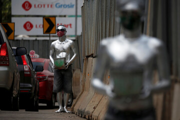 Men, known as 'Silver Men', wearing protective masks and carrying baskets stand on the side of a road while collecting alms from the motorists, following the coronavirus disease (COVID-19) outbreak, in Jakarta