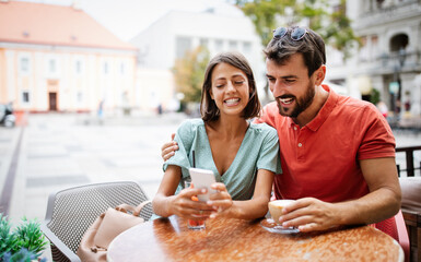 Embracing couple using mobile phone, smiling and talking in cafe