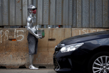 Man, known as 'Silver Man', wearing a protective mask and carrying a basket stands on the side of a road while collecting alms from the motorists, following the coronavirus disease (COVID-19) outbreak, in Jakarta