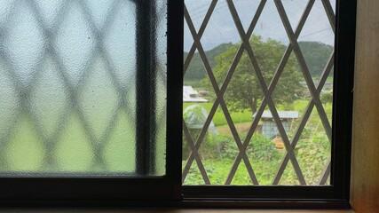 窓越しの畑とのどかな風景。地方移住/帰省イメージ写真素材。