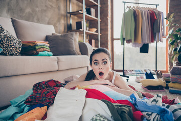 Photo of pretty displeased lady stay home quarantine lying many clothes heap stack floor wardrobe stuff pick select date look outfit confused have nothing to wear living room indoors