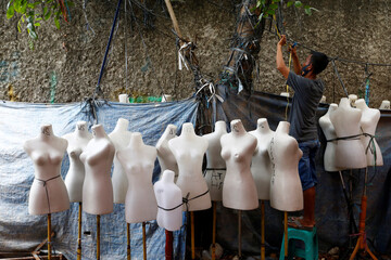 A man stands beside mannequins at Tanah Abang market amid the spread of the coronavirus disease (COVID-19) outbreak