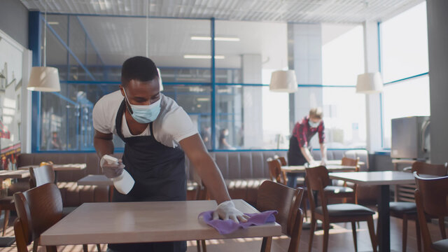 African male worker cleaning table with disinfectant in restaurant during coronavirus outbreak