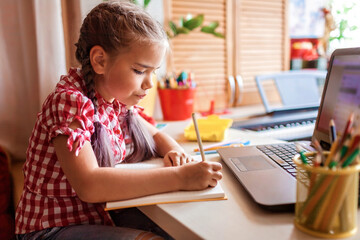 Distant education, back to school. Girl studying homework during online lesson at home