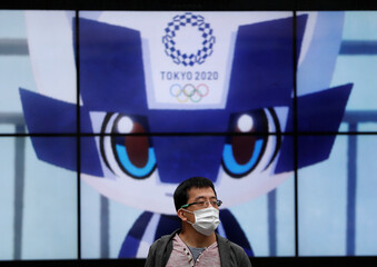 A man wearing a protective face mask stands in front of a screen showing Tokyo 2020 Olympic Games mascot Miraitowa amid the coronavirus disease (COVID-19) outbreak, in Tokyo