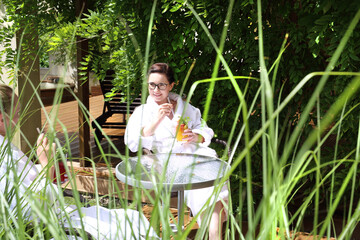 Weekend at the spa. A woman with a fruit cocktail is relaxing in a comfortable armchair. summer holidays. The woman is relaxing in the hotel garden.