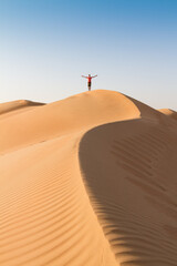 Male traveler standing on the top of dune, arms up to the sky, while traveling sand dessert in Oman. Travel adventure concept.