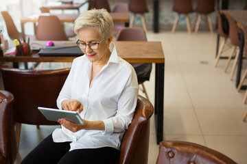 portrait of an adult stylish woman aged in a white shirt and glasses in the office with a tablet in...