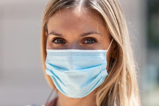 Beautiful blonde woman wearing protective mask on street.