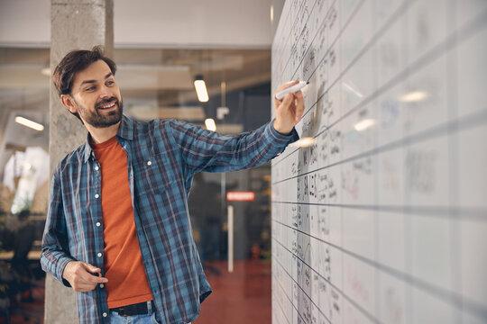 Joyful young man writing on whiteboard in office