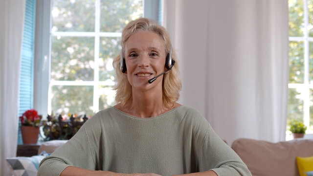 Senior woman in headset talking to client online at home office