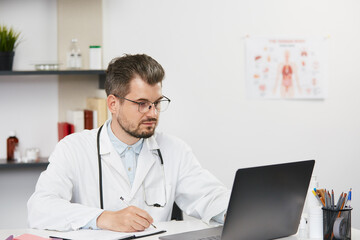 confident senior doctor working with laptop at medical cabinet