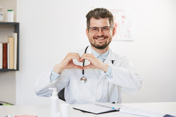 senior handsome doctor showing heart gesture
