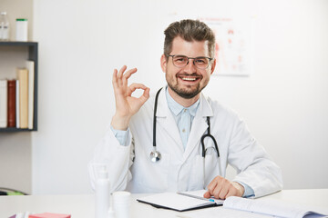 physician showing ok gesture and smiling to camera
