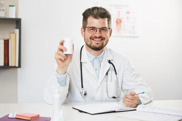 senior doctor holding jar of tablets sitting in medical cabinet