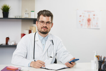 doctor holding smartphone sitting in medical cabinet