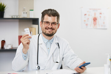 doctor holding tablets and smiling to camera