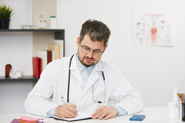 doctor writing in his notebook at medical cabinet