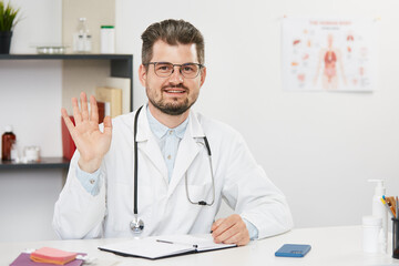 handsome senior doctor showing hi gesture while working online