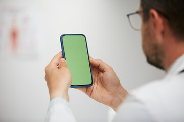 doctor holding green screen smartphone